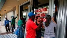 Fünf Männer und zwei Frauen schrauben Wellbleche an die Fassade eines Gebäudes im US-Bundesstaat Florida