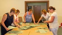 Fünf Frauen beugen sich über zusammengestellte Tische, auf denen hellgrüne Wahlzettel liegen
