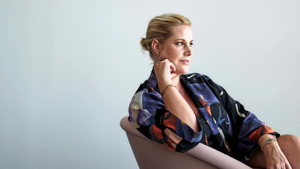 Anika Decker, auf einem Sessel sitzend