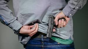 Waffenschein: Mann steckt sich eine Schreckschuss-Pistole in den Hosenbund.