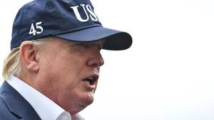 """Donald Trump im Profil. Er trägt ein blaues Jackett, ein weißes Hemd und ein blaues Cap mit """"USA"""" und """"45"""" Stickereien"""