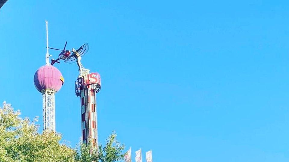 Ein Hubschraiber fliegt neben dem Turm eines Fahrgeschäfts, in dem Menschen festhängen