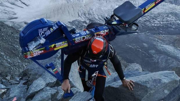Das undatierte Bild zeigt Matthew Paul Disney auf einem Berg mit einer Rudermaschine auf der Schulter