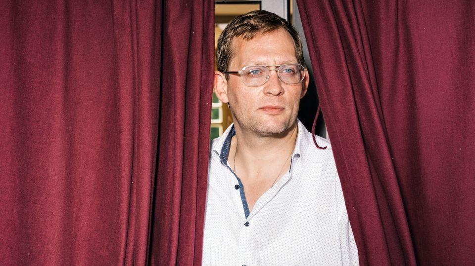 Erfolgsautor Clemens Meyer umrahmt von einem roten Vorhang