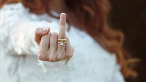 Eine Frau streckt den Ringfinger samt Verlobungs- und Ehering in die Höhe