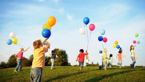 Kinder rennen mit Luftballons über eine Wiese