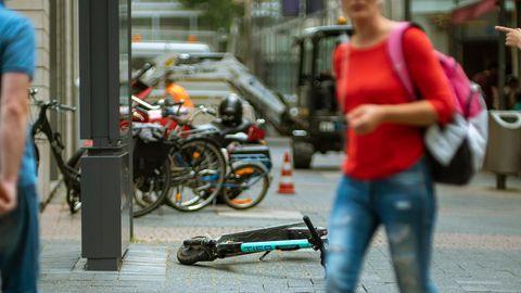 Ein E-Roller liegt mitten auf dem Gehweg