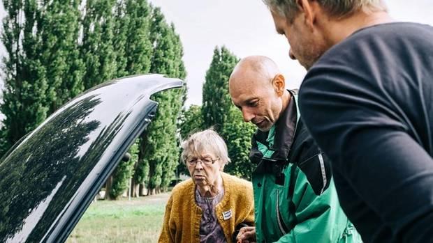 Frau Mulansky mit Fahrlehrer, auf den geöffneten Motorraum blickend