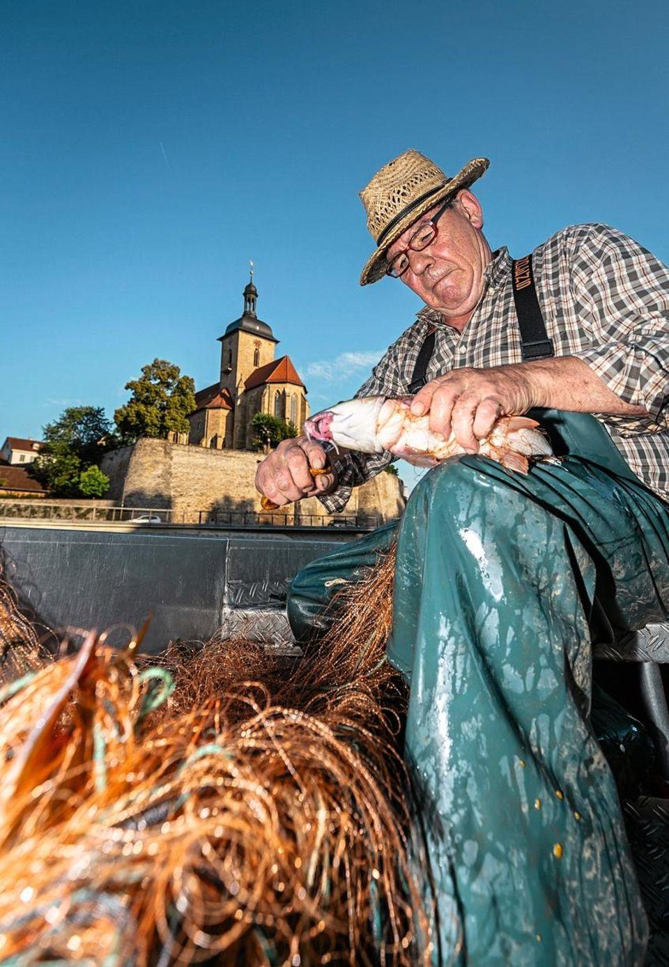 Jürgen Seybold sitzt, mit Fisch in der Hand, an seinem Netz