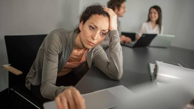 Eine gestresste Frau vor einem Laptop