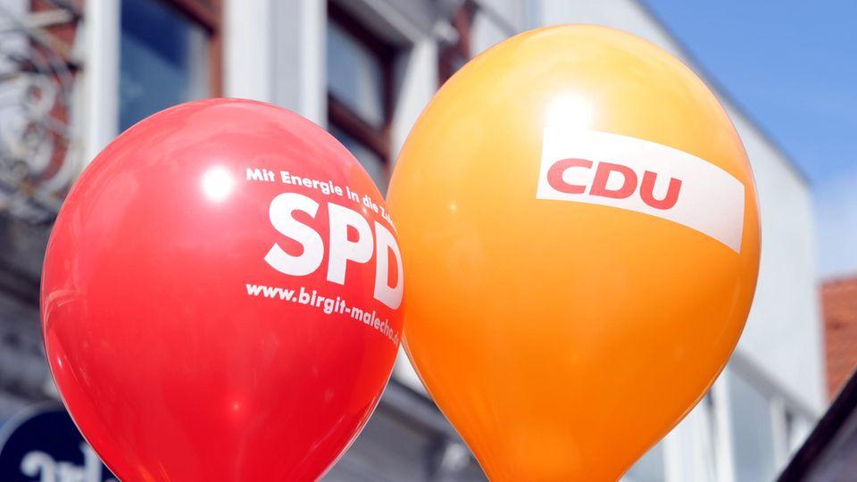 Ein SPD- und ein CDU- Luftballon schweben in der Innenstadt