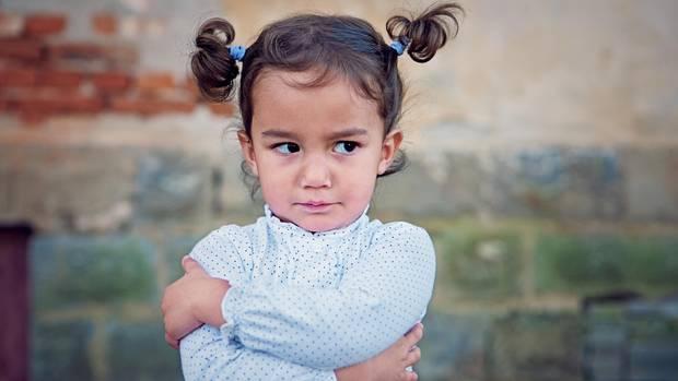 Ein kleines Mädchen guckt wütend mit verschränkten Armen