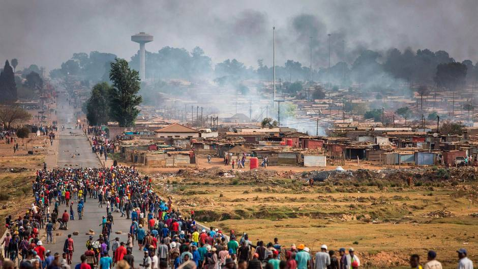Ein bewaffneter Mob rennt während einer neuen Welle von Gewalt gegen Ausländer durch Johannesburgs Katlehong Township