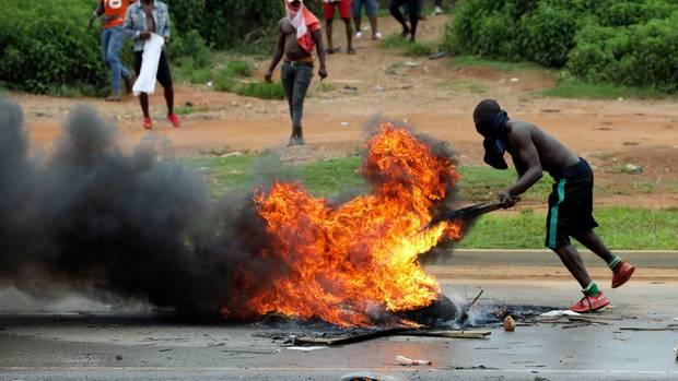 Ein Mann hält vor einer Filiale der Supermarktkette Shoprite in Abuja ein brennendes Stück Holz vor einem Feuer