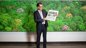 """Entwicklungsminister Gerd Müller hält ein Schild mit der Aufschrift """"Grüner Knopf"""""""