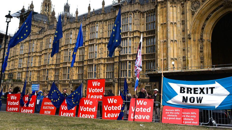 Menschen mit Pro-Brexit Plakaten stehen vor dem britischen Parlament