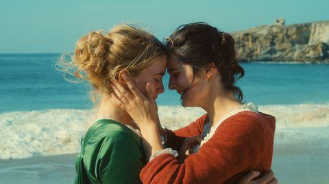 Zwei Frauen stehen, sich umarmend, am Meer
