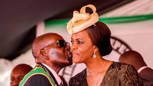 Robert Mugabe (l.) gibt seiner Frau Grace ein Küsschen