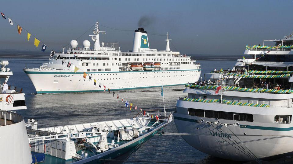 """Das Kreuzfahrtschiff """"Deutschland"""" fährt an der schon festgemachten """"Amadea"""" und """"Albatros"""" in Bremerhaven vorbei, um ebenfalls am Columbus-Kai festzumachen."""