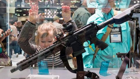 Ein junges Mädchen bestaunt auf dem jährlichen Treffen der NRA ein Gewehr.