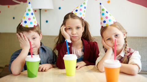 Drei Kinder mit Partyhütchen gucken genervt