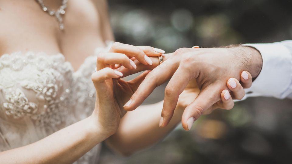 Hochzeit: Frau steckt Mann Ring an den Finger