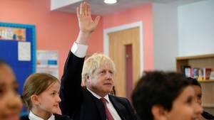 Boris Johnson, Premierminister von Großbritannien, hebt seinen Arm in einer Schulklasse