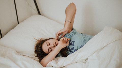 Frau liegt im Bett und räkelt sich.