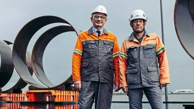 Ralf Hubo und Kay Lebenhagen vor riesigen Bauteilen für Windkraftanlagen