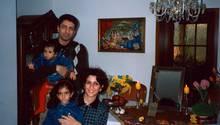 Sarah als kleines Kind auf dem Schoß ihrer Mutter. Dahinter ihr Vater, der ihre jüngere Schwester im Arm hält.