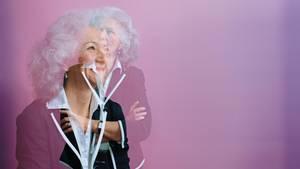 Dr. Hanna Ziegert vor einem lila Hintergrund. Bild ihresProfils, überlagert von einer Aufnahme, bei der sie nach oben blickt.