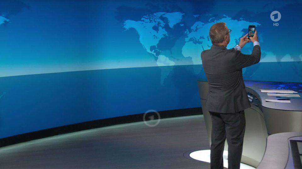 """Das Standbild von der ARD zeigt Sprecher Jan Hofer, der im Studio am Ende der """"Tagesschau"""" ein Selfie macht"""