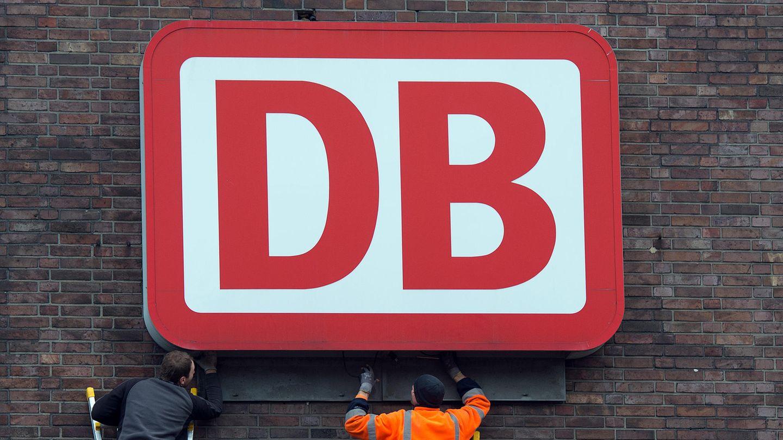 Monteure arbeiten an einem Unternehmensschild der Deutschen Bahn