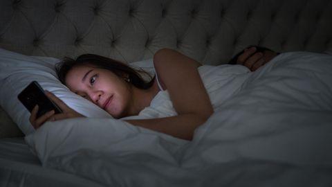 Eine Frau schaut nachts im Bett auf ihr Handy, der Mann schläft
