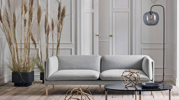 Ein helles Wohnzimmer mit einem Sofa und zwei Sessel in den Farben beige und braun