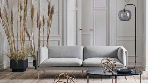 Ein helles Wohnzimmer mit einem grauen Sofa. Im Hintergrund ist eine schwarze Stehlampe zu sehen