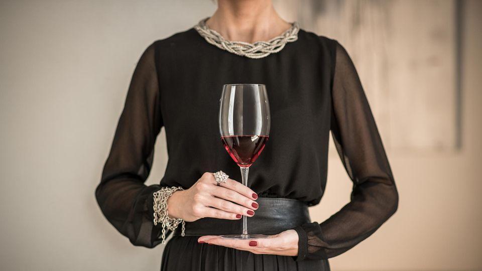 Schick gekleidete Frau hält ein mit Rotwein gefülltes Kristallglas vor ihrem Bauch