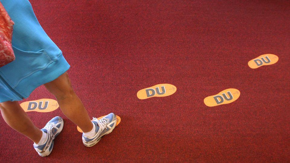 Orange Fußspuren mit Aufschrift Du auf rotem Teppichboden