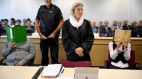 Mit verdeckten Gesichtern sitzen die Angeklagten zum Auftakt eines Mordprozesses im Gerichtssaal