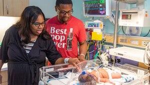 Eltern stehen am Bett ihres neu geborenen Babys