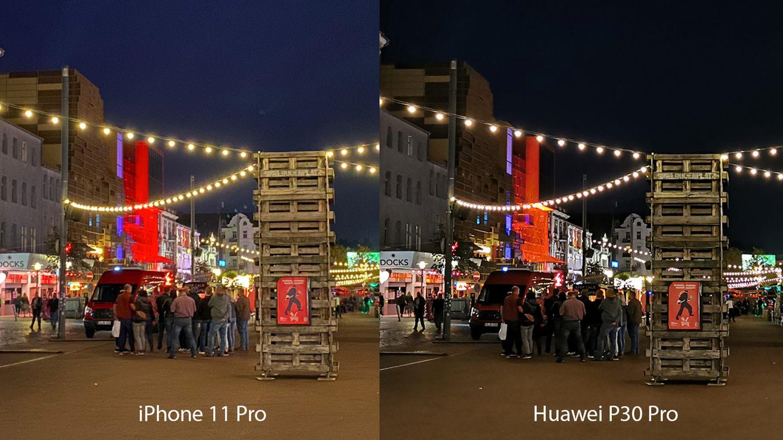 Huawei schärft seine Nachtaufnahmen generell sehr stark nach. Das sorgt einerseits für viele Details (Bretterwand im Vordergrund, beleuchtetes Haus im Hintergrund). Gleichzeitig verwaschen aber der Boden und die Klamotten der Menschen in der Mitte. Insgesamt ein Unentschieden.