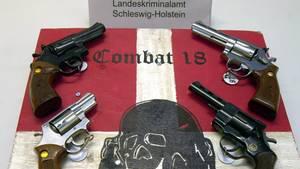 """Sichergestellte Waffen und ein Schild der kriminellen Neonazi-Gruppe """"Combat 18"""""""