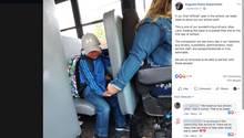 Vom Fahrersitz aus reicht eine Busfahrerin ihre Hand nach hinten zu einem weinenden Kind
