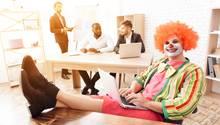 Ein Clown sitzt im Büro