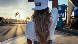 Model vor Sonnenuntergang mit weißer Cap