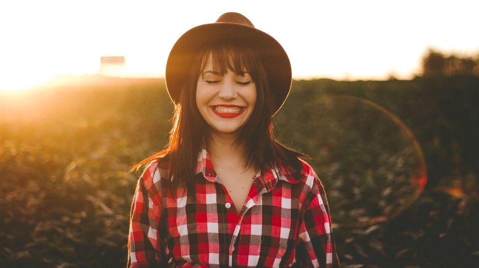 Junge Frau ist glücklich und lacht in die Kamera