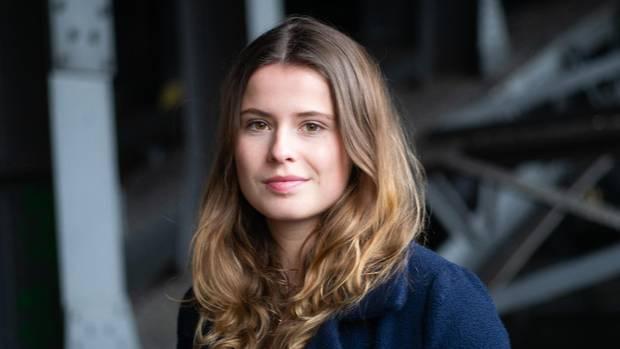 Luisa Neubauer trägt einen blauen Mantel und blickt in die Kamera
