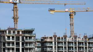 Kräne stehen auf einer Baustelle für Wohnhäuser in Hamburg