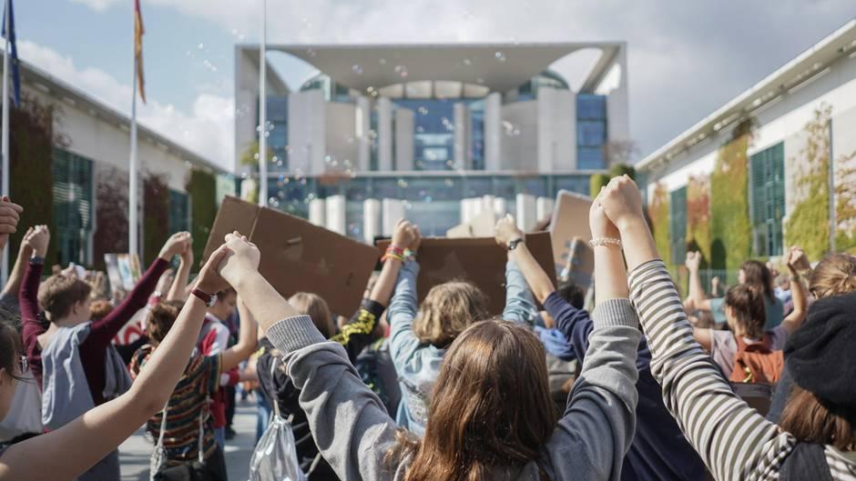 Teilnehmer einer Fridays for Future-Demonstration bilden eine Menschenkette vor dem Kanzleramt