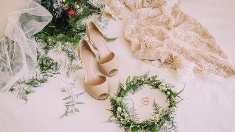 Braututensilien, wie ein Hochzeitskleid und Schuhe, liegen auf dem Boden